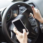 Woman sending text messages while driving.